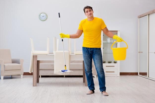 Man die het huis schoonmaakt dat zijn vrouw helpt Premium Foto