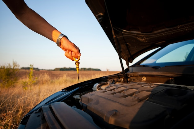 Man die het oliepeil van de motor controleert Gratis Foto