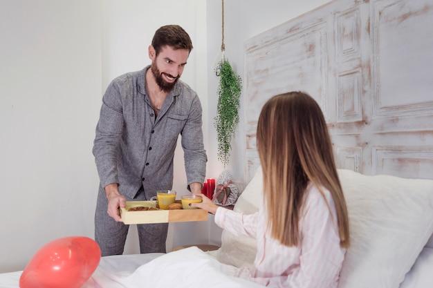 Man die houten dienblad met romantisch ontbijt geeft aan de vrouw Gratis Foto
