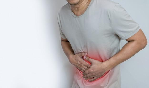 Man die lijdt aan buikpijn met beide handpalmen rond de taille om pijn en letsel op het buikgebied te tonen Premium Foto