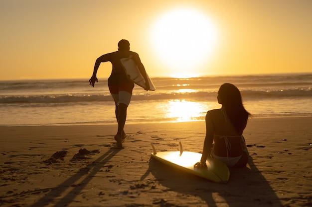 Man die met surfplank lopen terwijl vrouw het ontspannen op het strand tijdens zonsondergang Gratis Foto