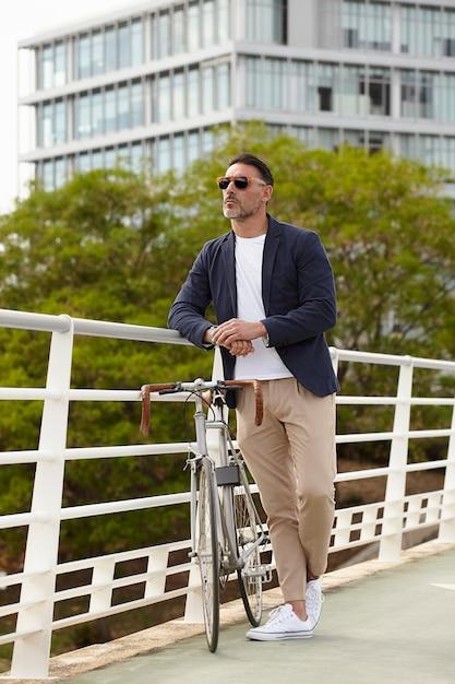 Man die naast zijn fiets staat Gratis Foto