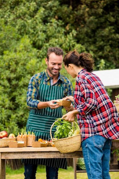 Man die organische groenten verkoopt aan vrouw Premium Foto