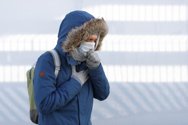 Man die verkouden is, zich onwel voelt, niest, hoest en een medisch gezichtsmasker draagt Premium Foto