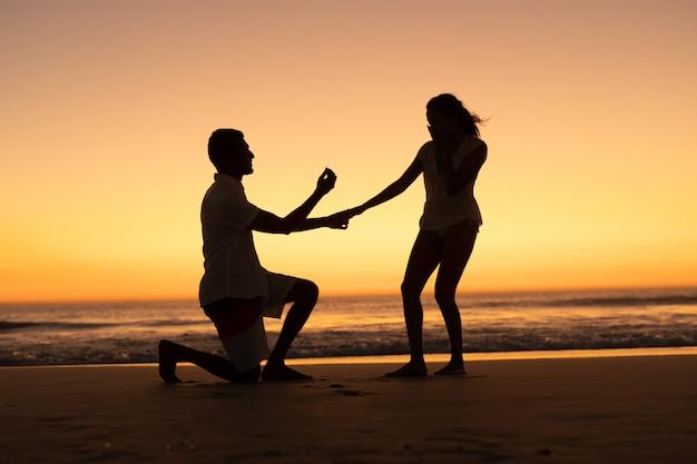 Man die vrouw voorstellen bij kust op het strand Gratis Foto