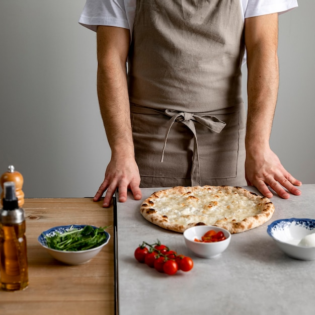 Man die zich dichtbij gebakken pizzadeeg met ingrediënten bevindt Gratis Foto
