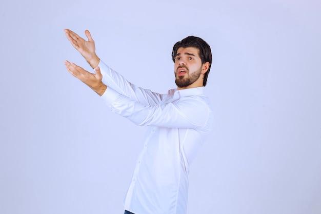 Man die zijn hand opheft en naar iets hierboven wijst. Gratis Foto