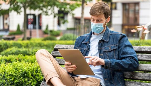Man die zijn tablet controleert terwijl hij een medisch masker draagt Premium Foto