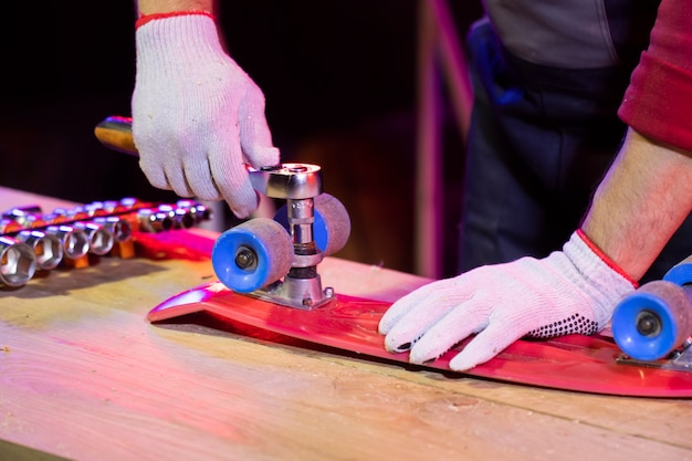 Man dient werkhandschoen in die rood plastic kindskateboard bevestigt Premium Foto