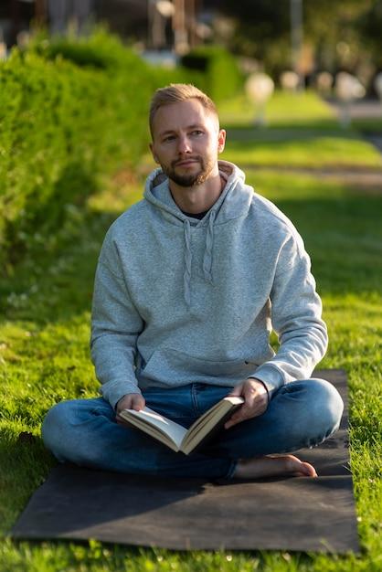 Man doet de lotushouding terwijl hij een boek vasthoudt Gratis Foto