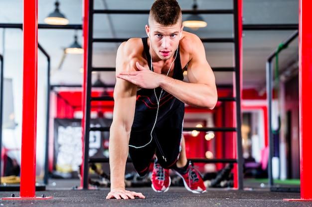 Man doet push-up in sport fitness gym Premium Foto
