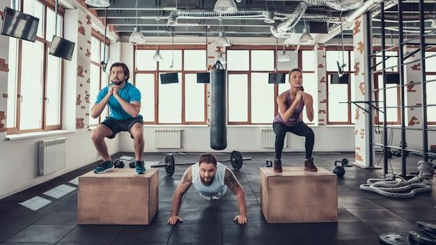 Man doet push-ups. jongen en meisje doen squats. Premium Foto