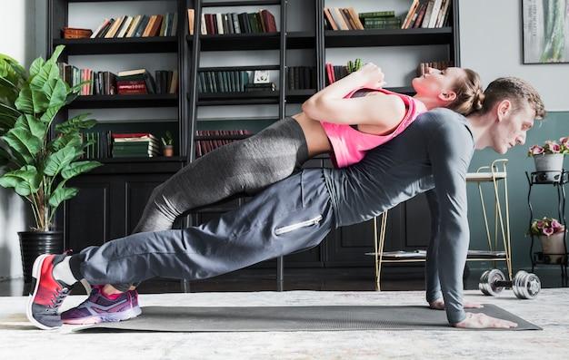 Man doet push ups met vrouw op rug Gratis Foto