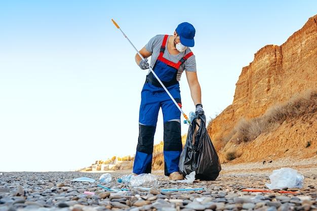 Man doet vrijwilliger bij het verzamelen van afval op het strand met een reikstok Premium Foto