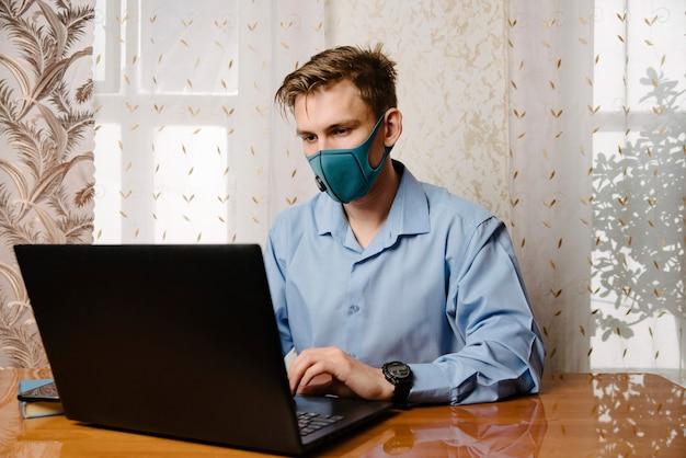 Man draag medisch masker werken met laptop. vermijd contact met andere mensen. blijf thuis. werken vanuit huis. Premium Foto