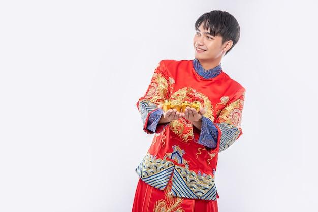 Man draagt cheongsam-pak en geeft goud aan zijn familielid voor geluk in chinees nieuwjaar Gratis Foto