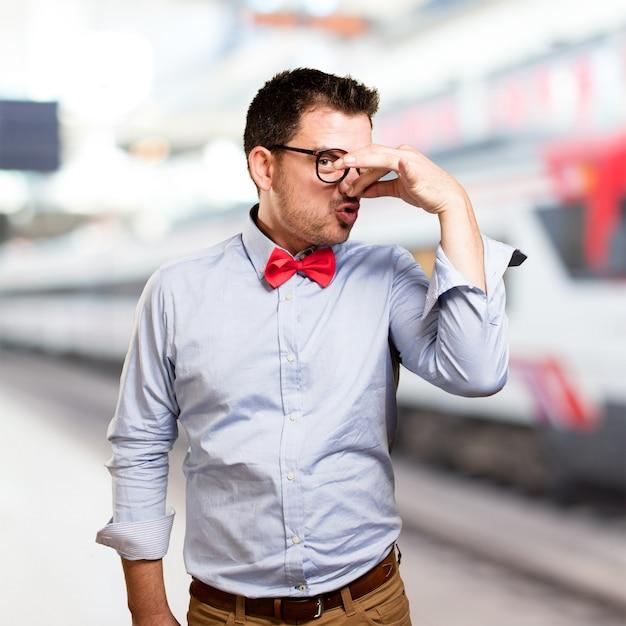 Man draagt een rode vlinderdas. doen slechte geur gebaar. Gratis Foto