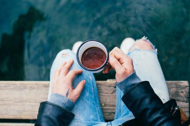 Man drinkt koffie uit emaille beker buitenshuis Gratis Foto