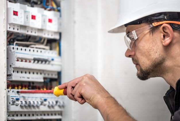 Man, een elektrotechnicus die in een schakelbord met zekeringen werkt. installatie en aansluiting van elektrische apparatuur. detailopname. Gratis Foto