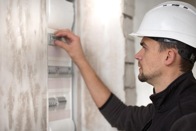 Man, een elektrotechnicus die in een schakelbord met zekeringen werkt. installatie en aansluiting van elektrische apparatuur. Gratis Foto