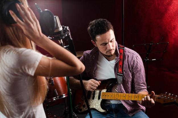 Man elektrische gitaar spelen en vrouw zingen Gratis Foto