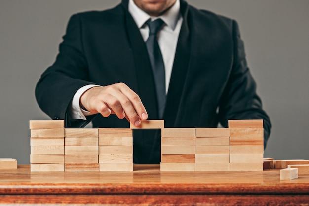 Man en houten kubussen op tafel. beheer concept Gratis Foto