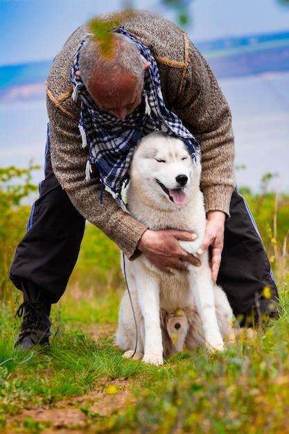 Man en husky hond wandelen in het park. Premium Foto
