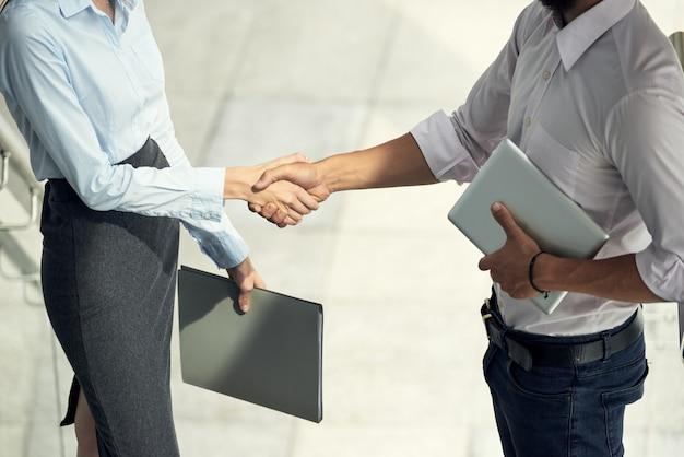 Man en vrouw begroeten elkaar schudden handen in kantoor Gratis Foto