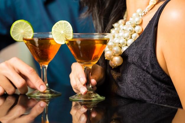 Man en vrouw bij bar met cocktails Premium Foto