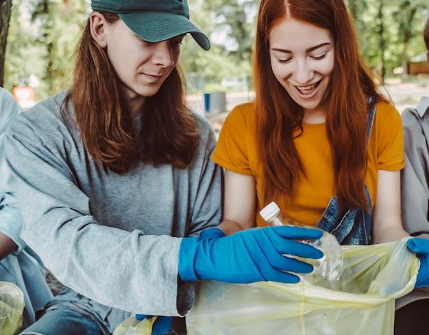 Man en vrouw die afval van het park opnemen. ze verzamelen het afval in een vuilniszak Gratis Foto
