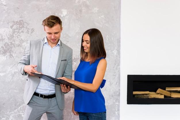 Man en vrouw die een klembord analyseren Gratis Foto