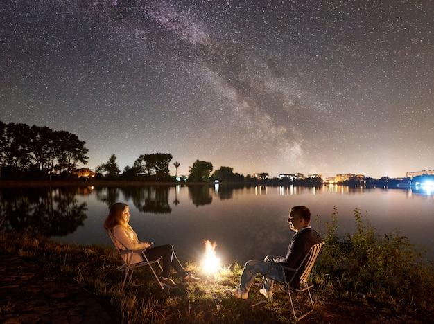 Man en vrouw die een rust op kust hebben onder nachthemel Premium Foto