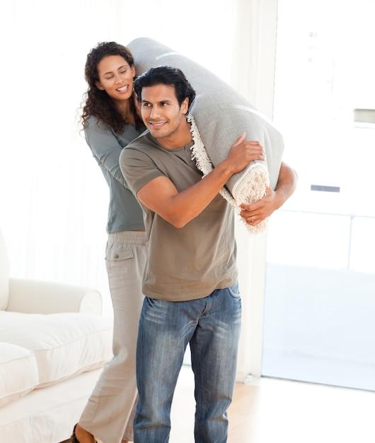 Man en vrouw die een tapijt samen dragen Premium Foto