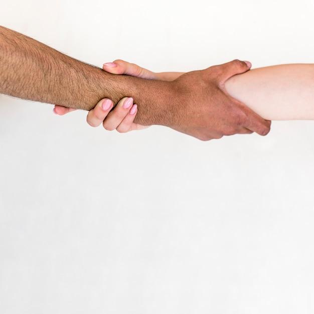 Man en vrouw die hun handen houden die over witte achtergrond worden geïsoleerd Gratis Foto