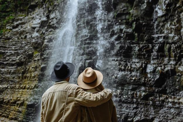 Man en vrouw die in bruin jasje waterval bekijken Premium Foto