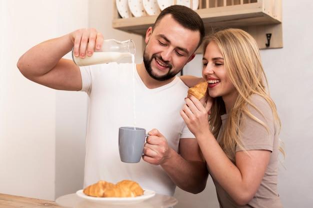 Man en vrouw die melk gieten en croissants eten Gratis Foto