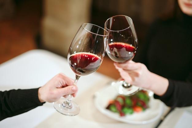 Man en vrouw die rode wijn drinken. op de foto, close-up handen met een bril. Premium Foto