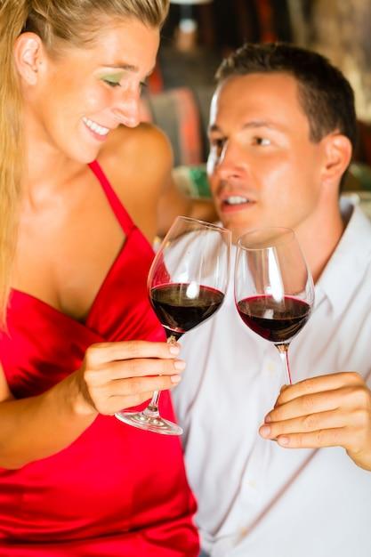Man en vrouw die wijn in kelder belasten Premium Foto