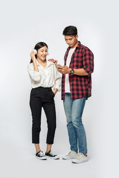Man en vrouw dragen shirts en luisteren naar muziek op smartphones Gratis Foto