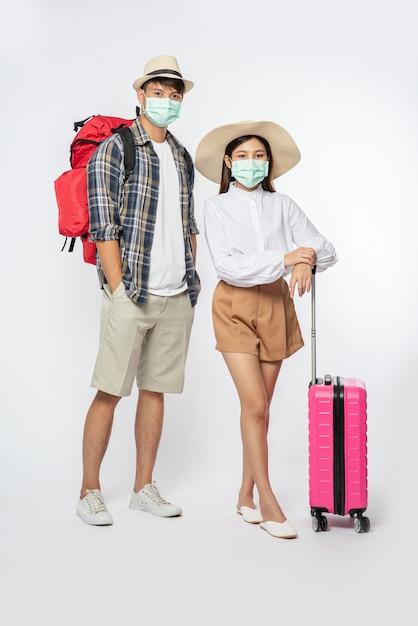 Man en vrouw gekleed om te reizen, met maskers en bagage Gratis Foto