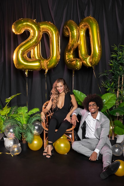 Man en vrouw glimlachen en nieuwjaar 2020 ballonnen Gratis Foto