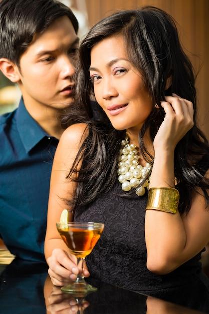 Man en vrouw in azië bij bar met cocktails Premium Foto