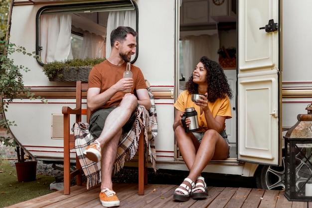 Man en vrouw koffie drinken in de natuur afstandsschot Gratis Foto