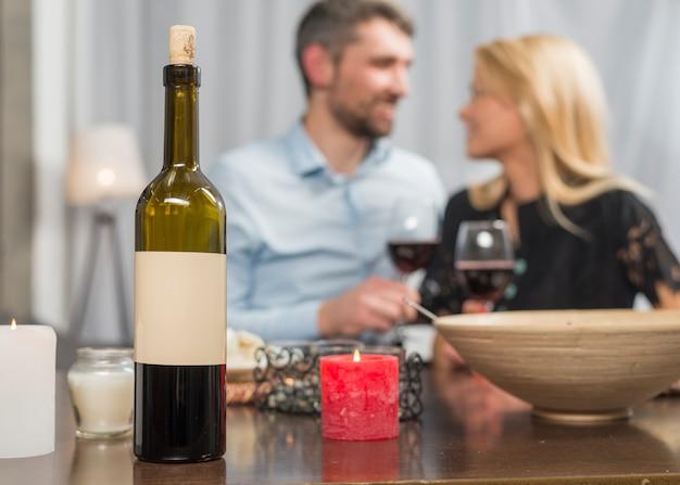 Man en vrouw met een bril aan tafel met fles en kom Gratis Foto