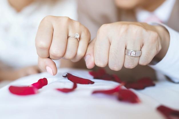 Man en vrouw met trouwring. jong echtpaar hand in hand, ceremonie trouwdag. pas getrouwd paar handen met trouwringen. Premium Foto
