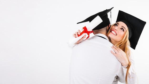 Man en vrouw omarmen met diploma's Gratis Foto