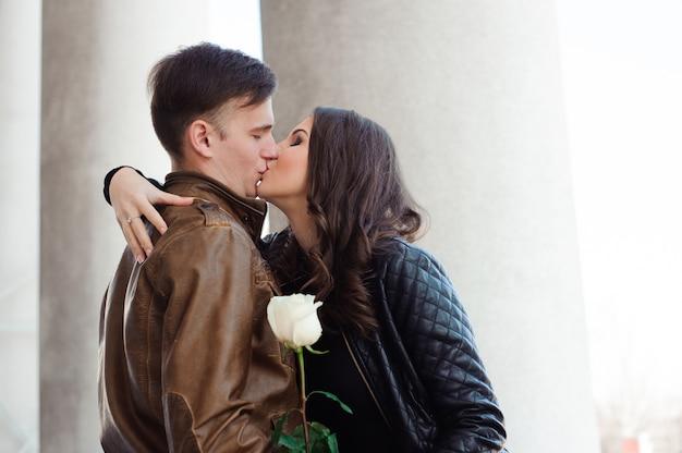Man en vrouw poseren op straat in de buurt van de kolommen van het theater Premium Foto