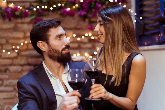 Man en vrouw rinkelende glazen drinken Gratis Foto