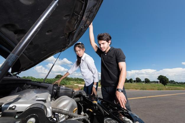Man en vrouw staan bij de kapotte auto en weten niet wat ze moeten doen Premium Foto