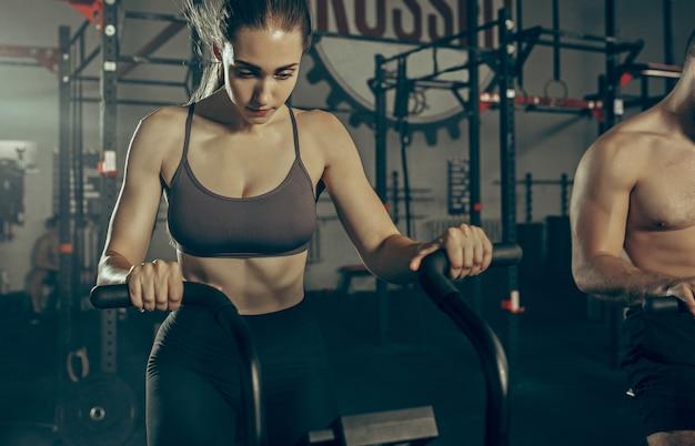 Man en vrouw tijdens oefeningen in de fitnessruimte. Gratis Foto